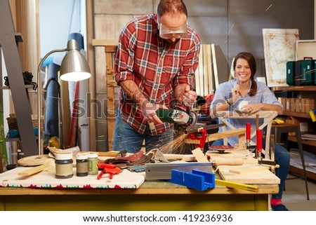 Man using hand saw, woman watching from background. - stock photo