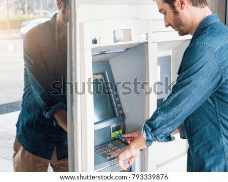 Man using his credit card in a bancomat atm for cash withdrawal