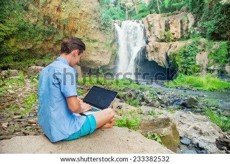 man using his laptop in a jungle - stock photo
