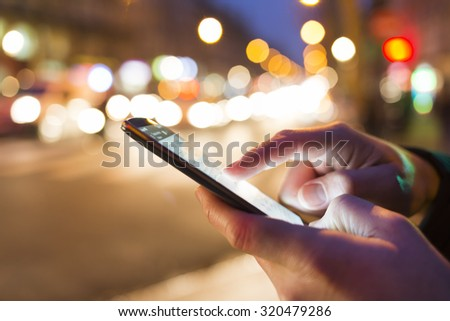 Man using his Mobile Phone in the street, night light bokeh Background - stock photo