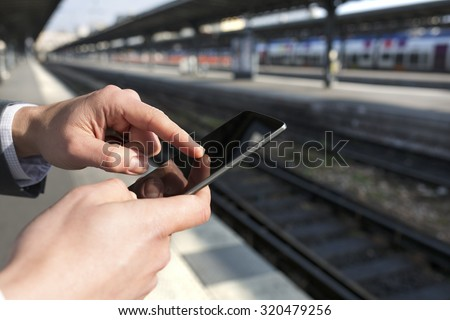 Man using his mobile phone on empty railway platform. Close-up hands - stock photo