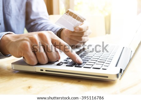 Man using laptop and mobile phone to online shopping and pay by credit card. Vintage tone, Retro filter effect, Soft focus, Low light. - stock photo