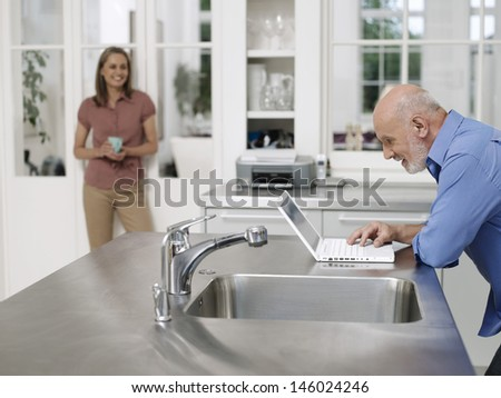 Man using laptop by kitchen sink as woman watching from distance - stock photo