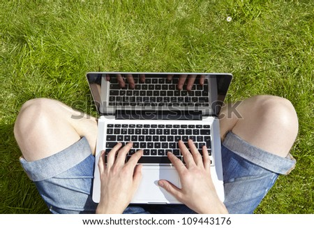 Man using laptop on a summers day sitting outside on grass - stock photo