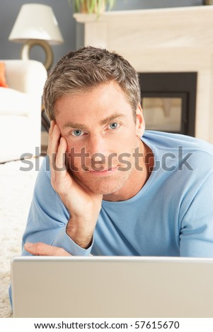 Man Using Laptop Relaxing Laying On Rug At Home - stock photo