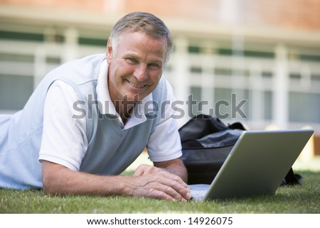 Man using laptop while lying in grass on campus - stock photo