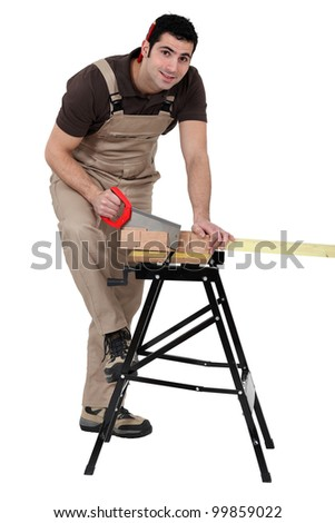 Man using miter to saw wood - stock photo