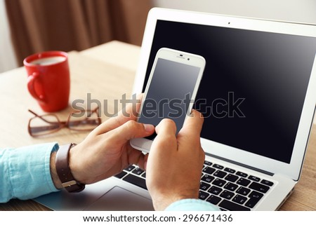 Man using mobile phone in office - stock photo