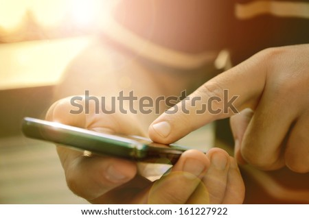 Man using mobile smart phone outdoor - stock photo