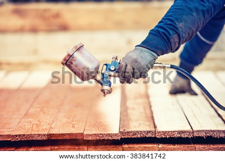 Man using protective gloves painting wooden timber with spray paint gun - stock photo