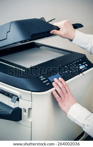 Man using scanner multifunction device in office - stock photo