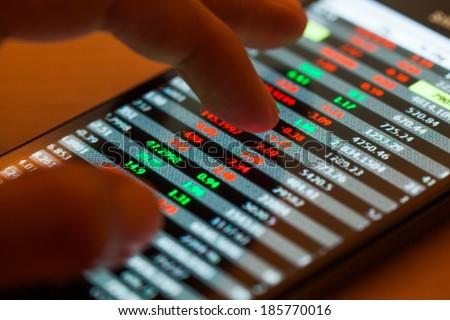 Man using smartphone, Stock market data - stock photo