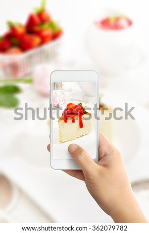 man using smartphones to take photos of japanese cheese cake with strawberry sauce with instagram style filter and later posted as food porn  - stock photo