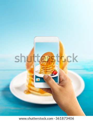 man using smartphones to take photos of pancake with butter and honey topping in blue background and blue wooden table with instagram style filter and later posted as food porn - stock photo