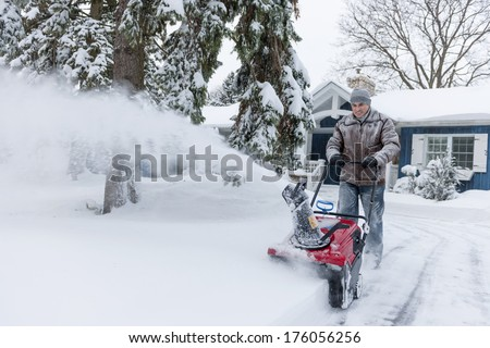Man using snowblower to clear deep snow on driveway near residential house after heavy snowfall. - stock photo