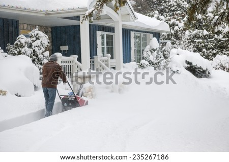 Man using snowblower to clear deep snow on driveway near residential house after heavy snowfall - stock photo