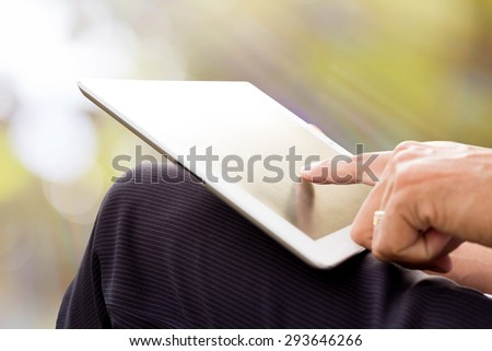 Man using tablet at sunset time - stock photo