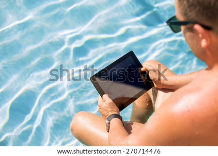 Man using tablet computer by the pool - stock photo