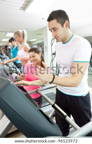 man using treadmill with personal trainer at gym - stock photo