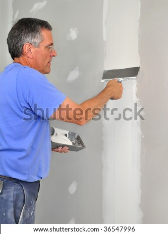 Man using trowel to finish seam between drywall panels - stock photo