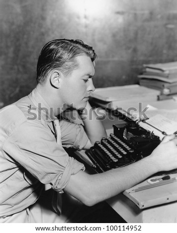 Man using typewriter - stock photo