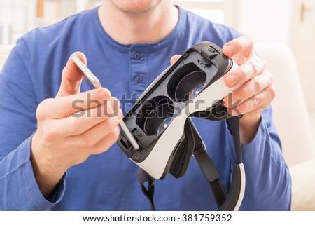 Man using virtual reality headset at home - stock photo