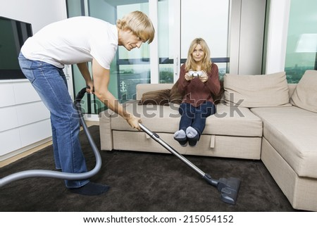 Man vacuuming while woman play video game in living room at home - stock photo