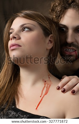 man vampire bites the neck of a woman