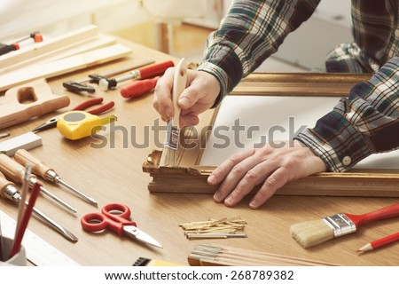 Man varnishing a wooden frame hands close up with DIY tools on a work table - stock photo