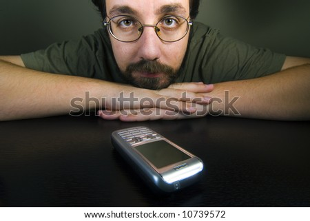 man waiting for a call while the mobile is in the table