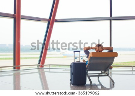 man waiting for his flight at the airport on lounge chair - stock photo
