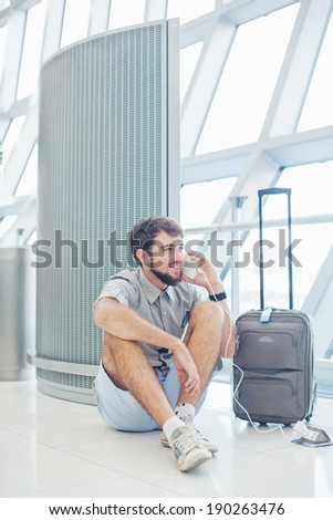 man waiting for his flight in the international airport and calling on phone - stock photo