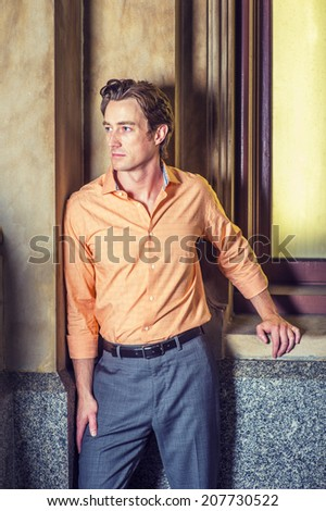 Man waiting for you. Dressing in a light orange patterned shirt, gray pants, a young handsome guy is standing by an old fashion window in the corner, looking away, relaxing. - stock photo