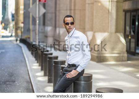 Man Waiting for You. Dressing in a white shirt, black pants, wearing sunglasses, a young, mysterious guy is sitting on the street, relaxing and waiting for you. - stock photo