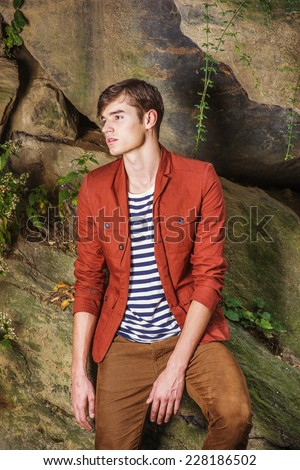 Man Waiting for You. Wearing a dark reddish brown jacket, unbuttoned, striped under shit, brown corduroy pants, a young handsome guy is standing by rocks, looking away, sad, thinking, lost in thought. - stock photo