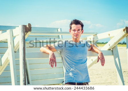 Man waiting for you. Wearing a gray t shirt, arms resting on a wooden stick, a young handsome guy is standing by a wooden structure on the beach, narrowing eyes, charmingly looking at you. - stock photo