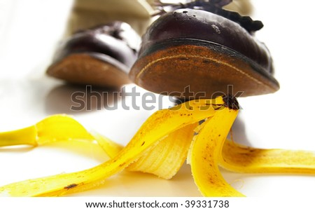 man walking, about to step on a banana peel - stock photo