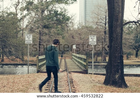 Man walking across a small railroad track in a park