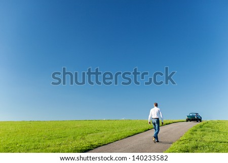 Man walking along a tarred road running through a green field towards his cabriolet car parked on the horizon against a sunny blue sky - stock photo