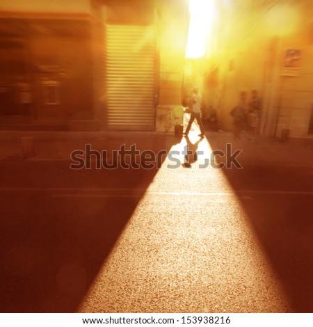 Man walking along the street at sunset light. - stock photo
