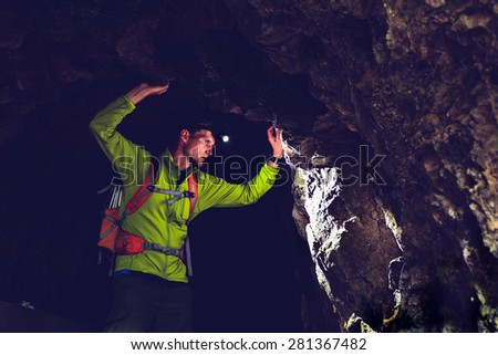 Man walking and exploring dark cave with light headlamp underground. Mysterious deep dark, explorer discovering mystery moody tunnel looking on rock wall inside. - stock photo