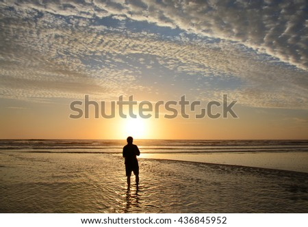 Man walking and relaxing on beach at sunrise, beautiful cloudy sky and sun reflected on the beach, Jacksonville, Florida, USA. - stock photo