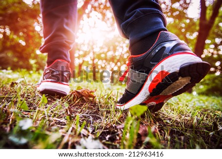 man walking cross country and trail in spring forest - stock photo