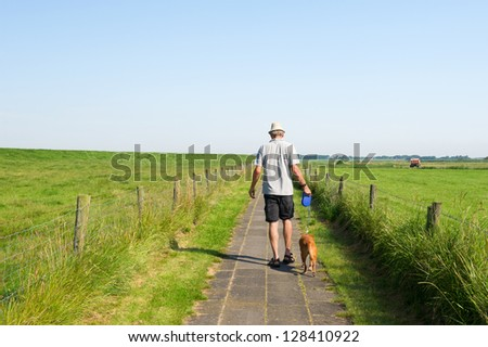 man walking his dog in agricultural landscape - stock photo
