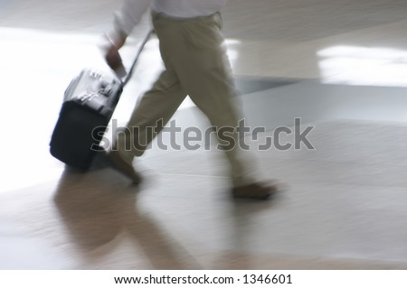 Man walking hurriedly at the airport terminal with his luggage - stock photo