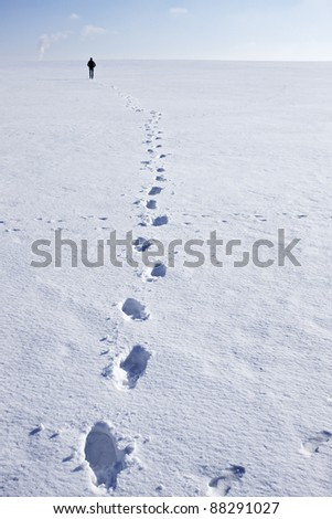 Man walking i snow making foot prints - stock photo