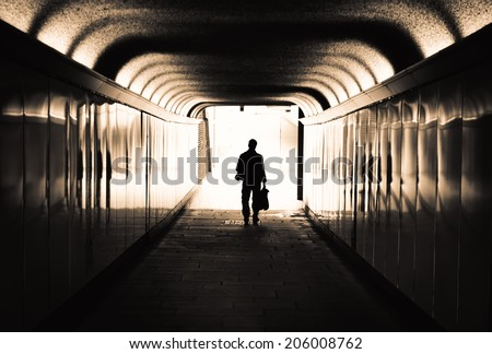 Man walking in a tunnel towards the light - stock photo