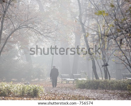 Man walking in foggy forest, or park - stock photo