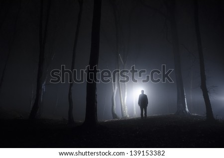 man walking in spooky forest at night - stock photo