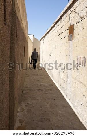 Man walking narrow street in the Old Town - stock photo